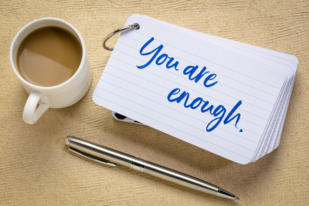 you are enough concept - handwriting on a stack of index cards with a cup of coffee and a pen against textured bark paper