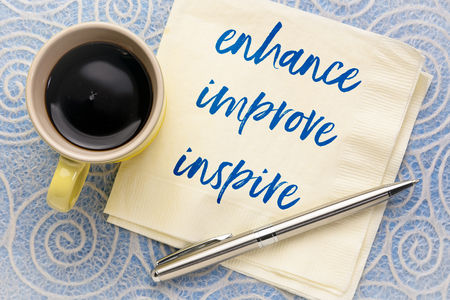 enhance, improve, inspire - handwriting on a napkin with a cup of coffee