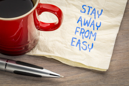 Stay away from easy advice or reminder - handwriting on a napkin with a cup of coffee