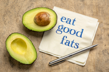 eat good fats, healthy eating concept - handwriting on napkin with a cut avocado against bark paper Stock Photo