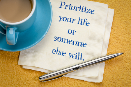 prioritize your life or someone else will - inspirational handwritingon a napkin with a cup of coffee