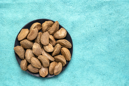 Brazilian nuts on a black plate against turquoise textured paper background with a copy space