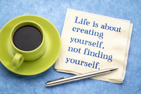 La vita consiste nel creare te stesso, non nel trovare te stesso: una calligrafia ispiratrice su un tovagliolo con una tazza di caffè Archivio Fotografico