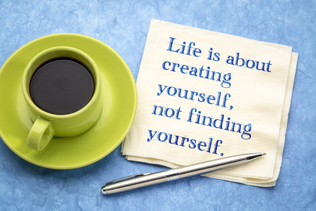 Life is about creating yourself, not finding yourself - inspirational handwriting on a napkin with a cup of coffee
