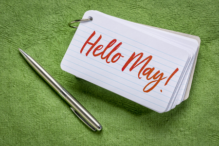 Hello May - handwriting on an index card with a pen against green textured paper