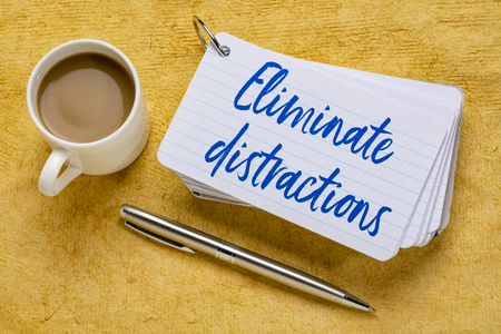Eliminate distractions - handwriting on a stack of index cards with a cup of coffee and  a pen against yellow textured paper Imagens