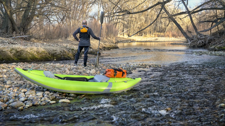 paddler with his whitewater inflatable kayak on a river  shore - Poudre River in Fort Collins, Colorado in early spring scenery and low water