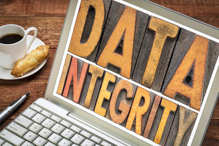 data integrity - word abstract in vintage letterpress wood type on a laptop with a cup of coffee Stock Photo