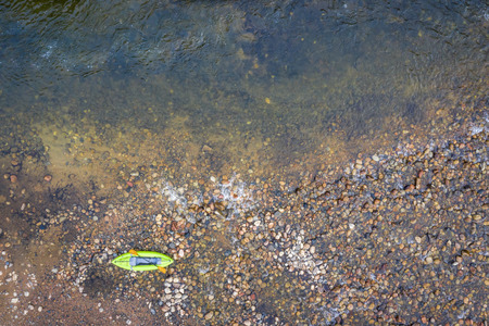 inflatable whitewater kayak on a rocky shore of mountain river (Poudre River in Colorado), aerial perspective