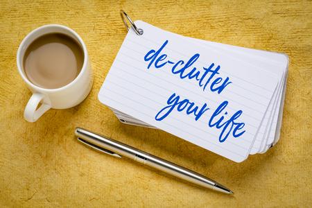 Entrümpeln Sie Ihr Leben - Handschrift auf einem Stapel Karteikarten mit einer Tasse Kaffee und einem Stift auf gelbem strukturiertem Papier Standard-Bild