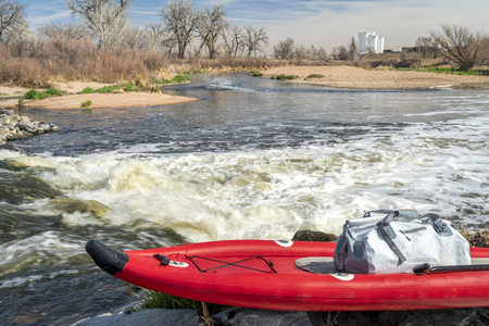 inflatable stand up paddleboard on a shore of the South Platte River in northern Colorado in early spring scenery Stock Photo