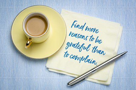 find more reasons to be grateful than to complain - inspirational handwriting on a napkin with a cup of coffee Фото со стока