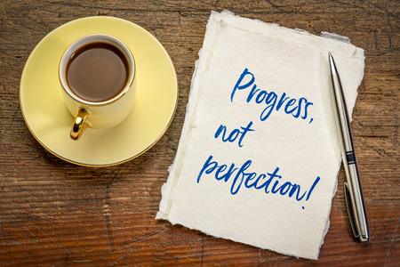 vooruitgang, geen perfectie inspirerend handschrift op een vel Khadi-papier met een kopje espressokoffie Stockfoto