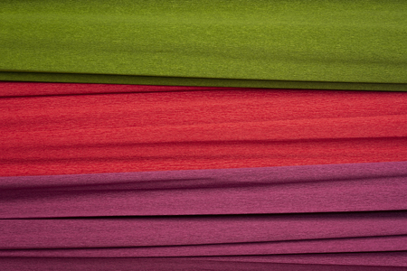 red, green and purple crepe paper - background with crinkled texture
