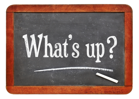Whats up? Informal, casual or urban slang greeting - white chalk text on a vintage slate blackboard