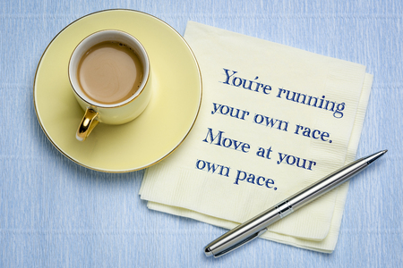 Youre running your own race. Move at your own poace. Inspirational handwriting on a napkin with a cup of coffee.
