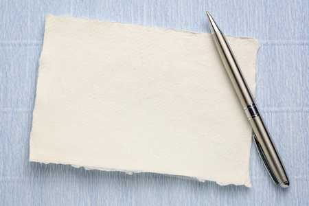small sheet of blank white Khadi rag paper from South India against blue Italian crepe paper with a metal pen