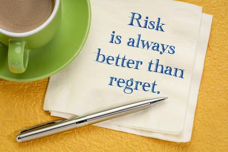 Risiko ist immer besser als Reue - inspirierende Handschrift auf einer Serviette bei einer Tasse Kaffee