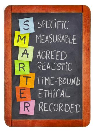 SMARTER (spezifisch, messbar, vereinbart, realistisch, zeitgebunden, ethisch, aufgezeichnet) - Akronym für Zielsetzungsmethodik, weiße Kreidehandschrift, bunte Haftnotizen auf isolierter Tafel