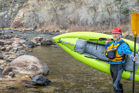 happy senior paddler carrying inflatable whitewater kayak on a shore of mountain river in early spring - Poudre River above Fort Collins, Colorado Stock Photo