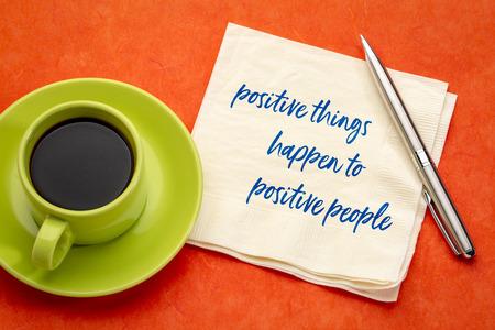 A las personas positivas les suceden cosas positivas: escritura a mano en una servilleta con una taza de café, concepto de ley de atracción Foto de archivo