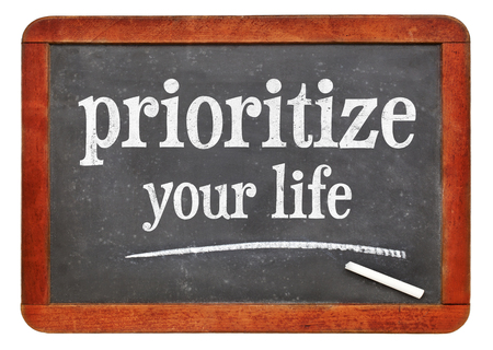 Prioritize your life advice - white chalk text on a isolated vintage slate blackboard