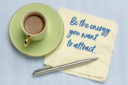 Sea la energía que desea atraer: escritura a mano en una servilleta con una taza de café, concepto de ley de atracción Foto de archivo