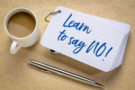 Learn to say no  advice or reminder- handwriting on a stack of index cards with a cup of coffee and a pen against textured bark paper