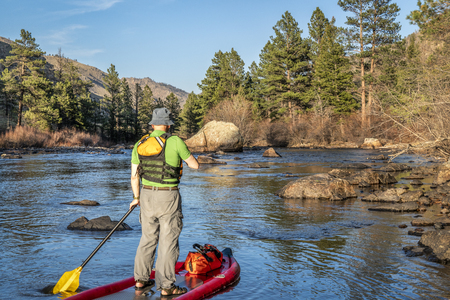 senior male paddling inflatable stand up paddleboard through a rock garden on a mountain river - Poudre RIver in Colorado in spring scenery with low water flow