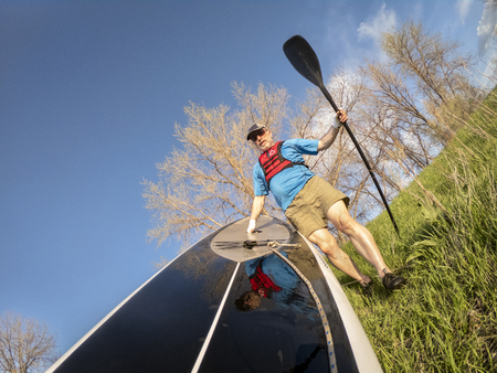 senior paddler wearing inflatable life jacket and paddling gloves is launching his stand up paddleboard on a lake, POV image with action camera wide angle distortion Reklamní fotografie
