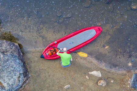 senior male paddler with inflatable whitewater stand up paddleboard on a shore of mountain river - Poudre River in Colorado, aerial view