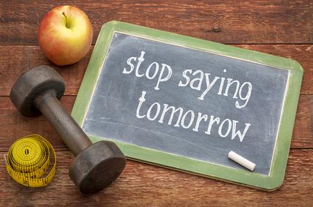 Hör auf, morgen zu sagen - weißer Kreidetext auf einer Schiefertafel gegen verwittertes rot lackiertes Scheunenholz mit Hantel, Apfel und Maßband