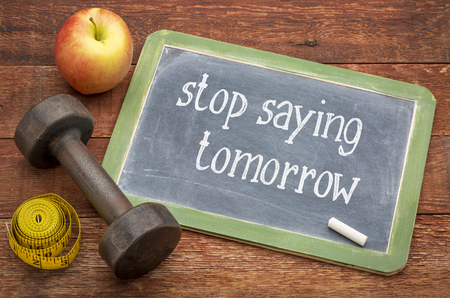 stop saying tomorrow - white chalk text on a slate blackboard against weathered red painted barn wood with a dumbbell, apple and tape measure