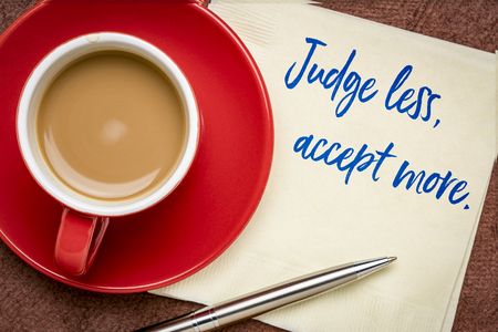 judge less, accept more - inspirational handwriting on a napkin with a cup of coffee