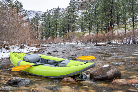 inflatable whitewater kayak with a paddle on shore of mountain river after springtime snowstorm - Poudre River in northern Colorado