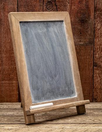 Signo de pizarra en blanco con manchas de tiza blanca contra la madera rústica del granero