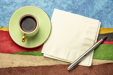 napkin, pen and a cup of coffee against abstract landscape created with sheets of textured colorful handmade paper 版權商用圖片