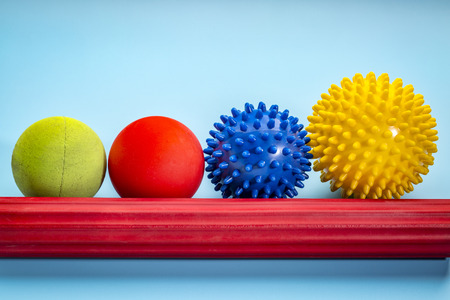 self massage and reflexology therapy concept - a set of small rubber balls and roller bar against blue background