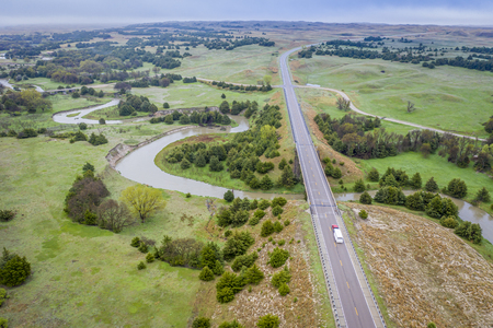 aerial view of a highway and bridge over the Dismal River in Nebraska Sandhills near Thedford, foggy morning spring scenery Stock Photo