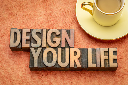 design your life  - word abstract in vintage mletterpress wood type with a cup of coffee