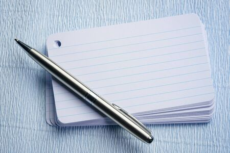 stack of blank index card with a pen over textured crepe paper
