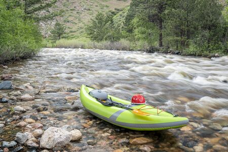 inflatable whitewater kayak on a shore of a mountain river - Poudre River in northern Colorado with high water flow Banco de Imagens