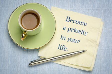 Become a priority in your life - inspirational handwriting on napkin with a cup of coffee