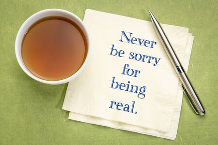 Never be sorry fro being real - inspirational handwriting on a napkin with a cup of tea.