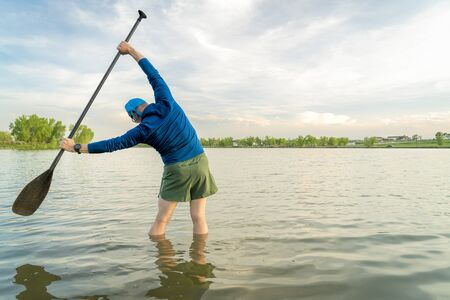 mature stand up paddler is stretching a on a lake shore after  paddling workout