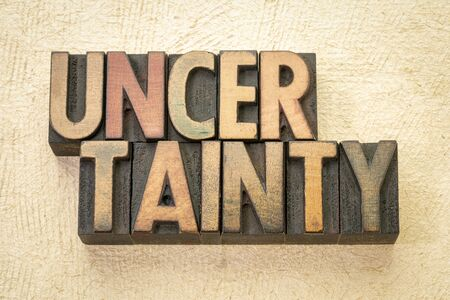 uncertainty word abstract in vintage letterpress wood type against textured paper