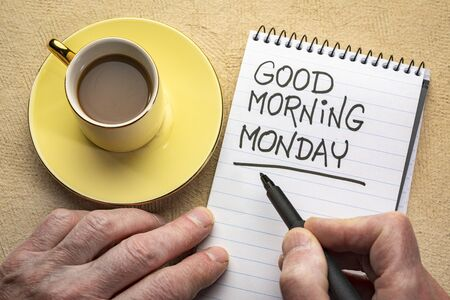 Good Morning Monday - man hand writing a note with a black marker in a spiral notebook, overhead view with a cup of coffee Reklamní fotografie