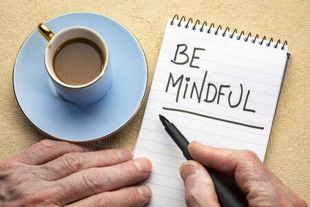 Be mindful - man hand writing a note with a black marker in a spiral notebook Stok Fotoğraf