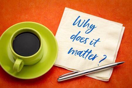 Why does it matter? Handwriting on a napkin with a cup of coffee.