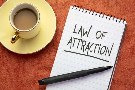 Ley de atracción: escritura a mano con marcador negro en un cuaderno de espiral con una taza de café